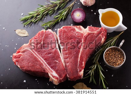 Raw fresh meat t-bone steak with spices, garlic and rosemary on a dark background - stock photo