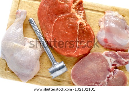 Raw fresh meat with hammer on wooden board - stock photo