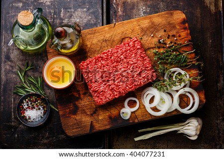 Raw fresh Minced meat forcemeat and condiments on dark background - stock photo
