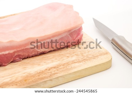 Raw fresh pork belly on cutting board with knife on white background - stock photo
