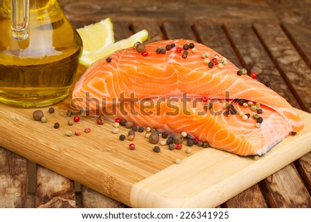 raw fresh salmon steak on wooden table with pepper corn - stock photo