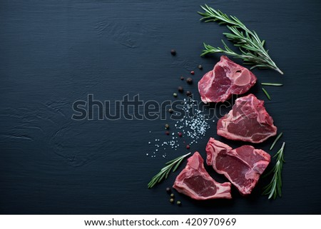 Raw fresh T-bone lamb steaks on a black wooden surface, top view
