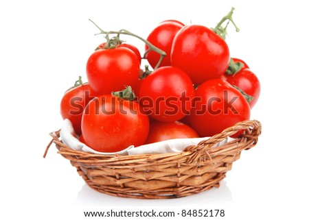 raw fresh tomatoes in wicker basket on green branch isolated on white background - stock photo