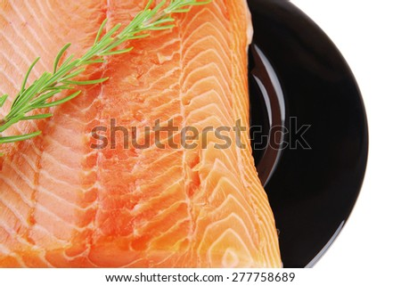 raw fresh uncooked salmon red fish fillet on black plate with rosemary twig isolated over white background - stock photo