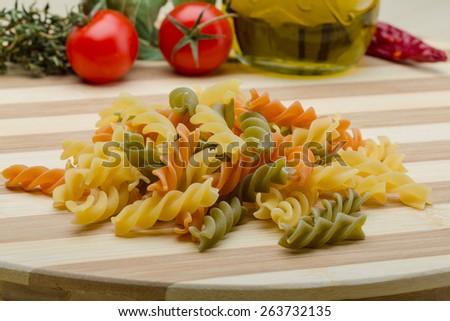 Raw fusilli pasta on the wood background - stock photo