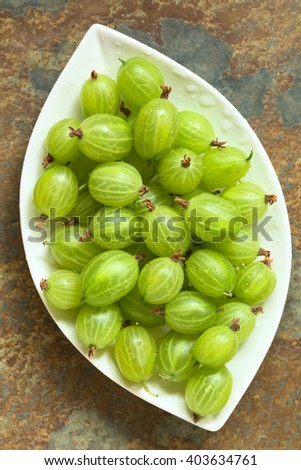 Raw gooseberries (lat. Ribes uva-crispa) on plate, photographed overhead on slate with natural light (Selective Focus, Focus on the gooseberries on the top) - stock photo