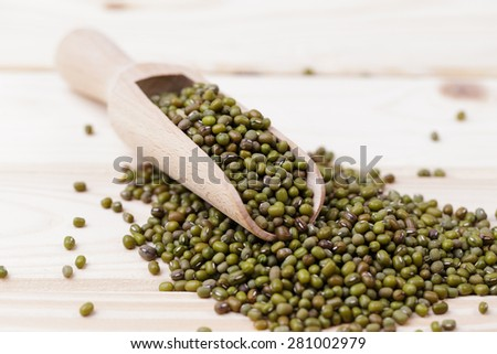 Raw green mung bean in wooden spoon closeup