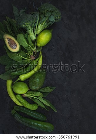 Raw green vegetables set. Broccoli, avocado, pepper, spinach, zucchini, lime on  dark stone background, top view, copy space - stock photo