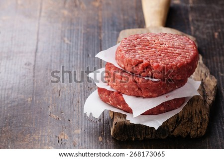 Raw Ground beef meat Burger steak cutlets on dark wooden background - stock photo