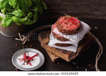 Raw Ground beef meat Burger steak cutlets with chili, basil and seasoning on  rustic wooden board over dark marble background - stock photo