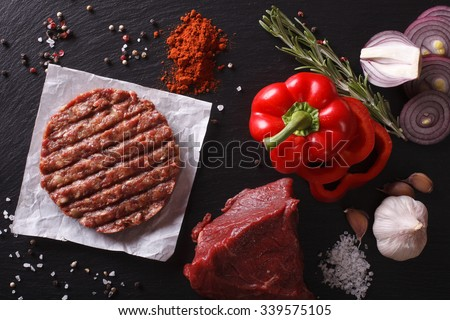 Raw Ground beef meat Burger steak cutlets with ingredients on the board. horizontal view from above - stock photo