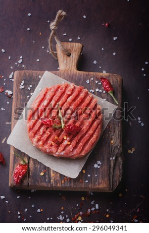 Raw Ground beef meat Burger steak cutlets with seasoning on vintage wooden boards, black background, top view - stock photo