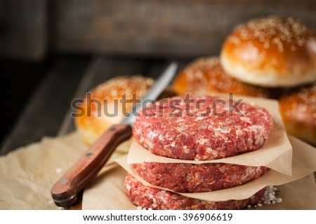 Raw ground beef meat steak cutlets and burger buns on  wooden background, ready for cooking - stock photo