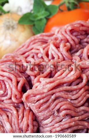Raw ground beef, with tomatoes, onion, garlic and herbs behind. - stock photo