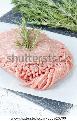Raw ground pork with rosemary - stock photo