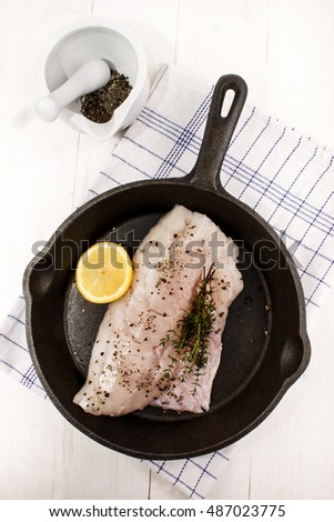 raw hake fillet with thyme, crushed peppercorn and a lemon slice in a cast iron pan