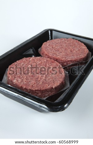 Raw hamburger patties in a black plastic tray. - stock photo