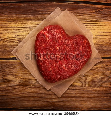 Raw heart shaped burger cutlet over grunge wooden background. Top view. Toned image. Square image - stock photo