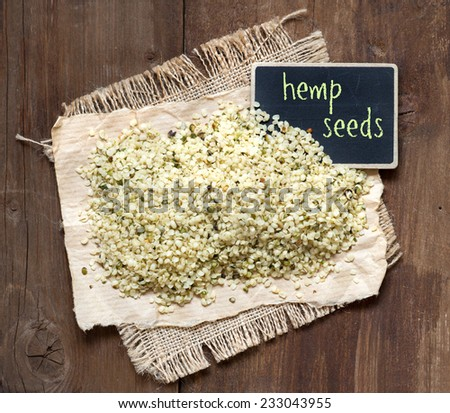 Raw hemp seeds with a small chalkboard on a wooden table - stock photo