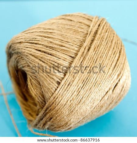 Raw hemp thread role isolated on blue background - stock photo