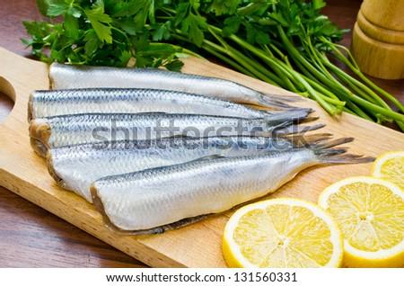 Raw herrings on wooden board - stock photo