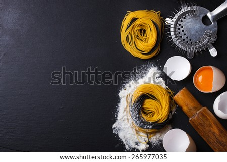 Raw homemade pasta and ingredients a black background.selective focus - stock photo