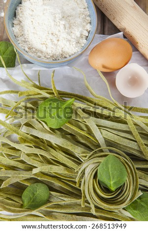 Raw homemade spinach pasta with spinach leaves, eggs, bowl of flour and rolling pin over the rustic wooden table