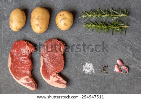 Raw ingredients for a steak diner laid out on a slate - stock photo