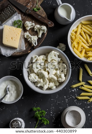 Raw ingredients for cooking pasta with roasted cauliflower - pasta, cauliflower, cheese, cream on dark stone background. - stock photo