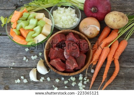 Raw ingredients to prepare a stew: beef, carrots, rutabaga, garlic, onions, celery, potato and sweet potato - stock photo