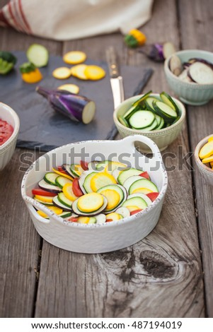 Raw ingredients zucchini, bell pepper, onion, eggplant, tomato sauce in gratin dish for traditional French ratatouille. Also available in horizontal format.