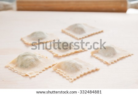 Raw Italian ravioli on natural wood working board with rolling p - stock photo