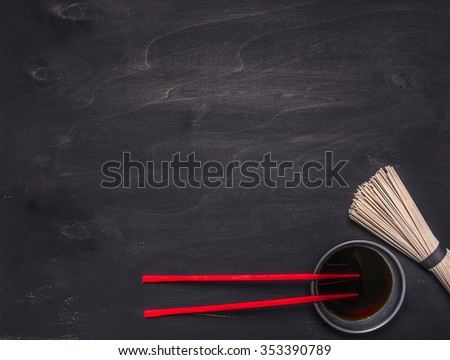 raw Japanese buckwheat noodles with soy sauce and red chopsticks place for text,frame on wooden rustic background top view - stock photo