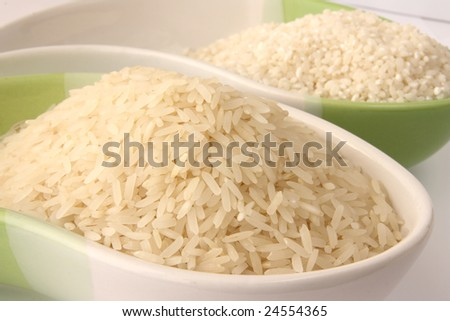Raw jasmin rice and arborio round risotto rice in bowls - stock photo