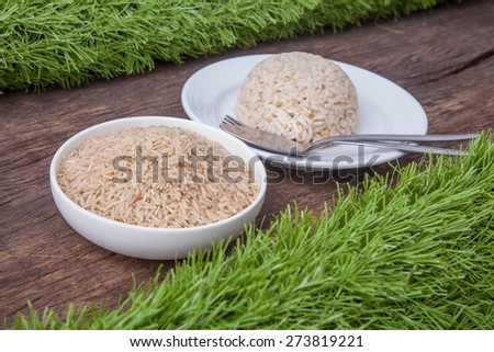 Raw jasmine brown rice in white bowl and background of cooked jasmine brown rice on white plate with spoon and fork on the side, on wooden table top decoration with green grass - stock photo
