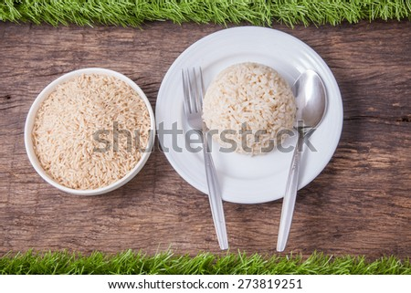 raw jasmine brown rice in white bowl and cooked jasmine brown rice on white plate with spoon and fork, on wooden table top decoration with green grass - stock photo