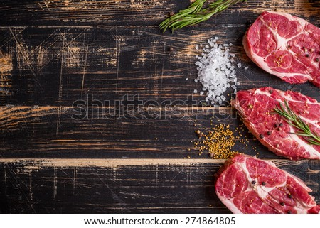 Raw juicy meat steak on dark wooden background ready to roasting - stock photo