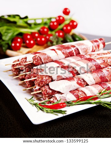 Raw kebab with chili, tomatos and lettuce served on plate - stock photo