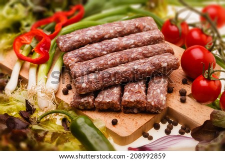 raw kebapcheta with vegetables on wooden board, selective focus - stock photo