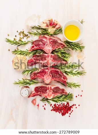Raw lamb  chop cutlet with oil , rosemary and garlic on white wooden background, top view - stock photo