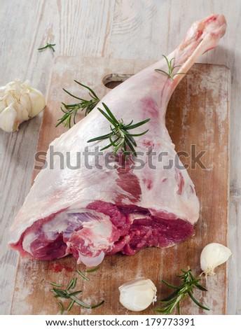Raw lamb leg on a wooden table. - stock photo