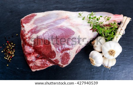 Raw lamb leg on blue stone background with herbs - stock photo