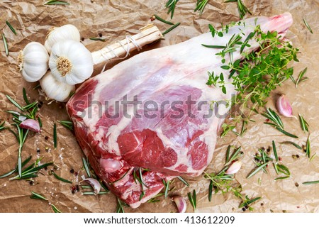 Raw lamb leg on crumpled paper background with herbs. - stock photo