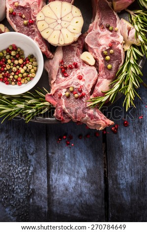 Raw lamb meat with peppercorn, rosemary and garlic on blue rustic wooden table, place for text - stock photo