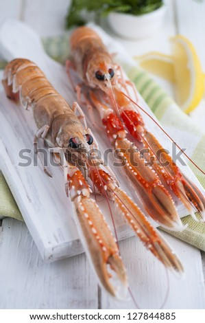 Raw langoustines with lemons and parsley on white board - stock photo