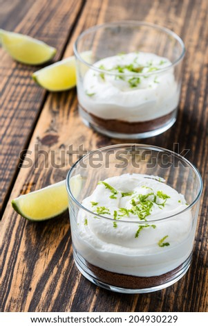Raw  lime cheesecake in a glass on wooden rustic table - stock photo
