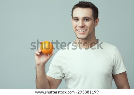Raw, living food concept. Portrait of happy young man wearing white t-shirt holding orange in hand over gray background. Casual clothing. Muscular body. Copy-space. Close up. Studio shot - stock photo