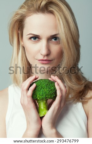 Raw, living food, veggie concept. Portrait of young woman with long blond hair holding bunch of broccoli in her hands over light gray background. Natural make-up. Close up. Studio shot