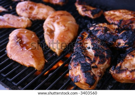 raw marinated chicken grilling on a barbecue - stock photo