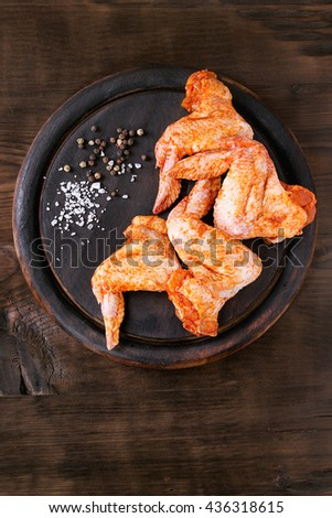 Raw Marinated chicken meat wings for BBQ, served on round wood chopping board with seasoning over dark wooden background. Top view with copy space. - stock photo